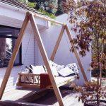 Balançoire de jardin avec cadre en bois sur la terrasse