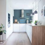 Belle cuisine lumineuse avec un magnifique mur bleu chaud. Les éléments de cuisine blancs et le…