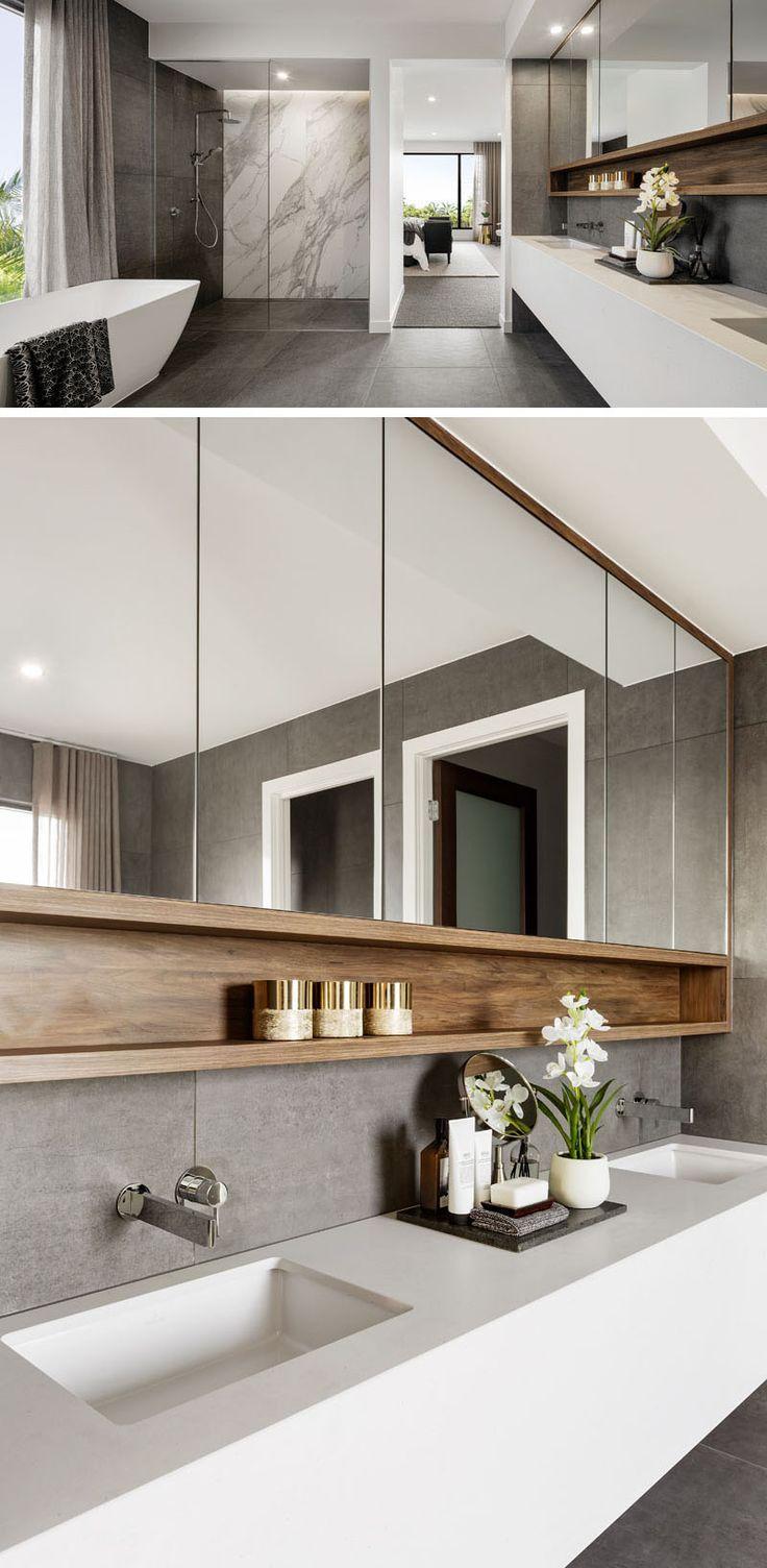 Cette salle de bain moderne a une grande douche, une longue