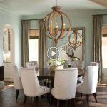 Les chaises en peluche contrastent avec la table à manger circulaire en bois sombre. Un grand...
