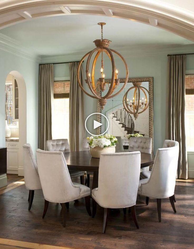 Les chaises en peluche contrastent avec la table à manger circulaire en bois sombre. Un grand…