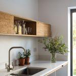 Un aménagement en bois suspendu au-dessus du plan de travail apporte à la cuis...