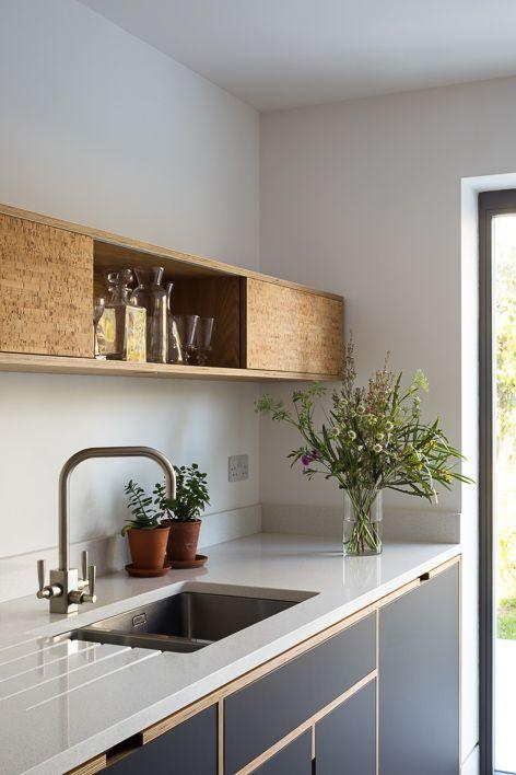 Un aménagement en bois suspendu au-dessus du plan de travail apporte à la cuis…