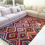 Bunter Teppich mit Zickzackmuster und Fransen für eine helle Couch