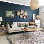 Eine dunkelblaue Akzentwand mit cremefarbenem Sofa, geflochtenen Korbkörben und ein