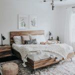 Neutrales Schlafzimmerdesign mit extra großem Teppich und Holzbett