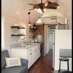 The farmhouse style tiny home features yellow pine hardwood floors shiplap sidin...